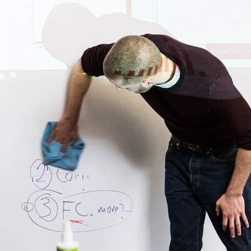työntekijä puhdistaa projektori-tussitaulutapettia