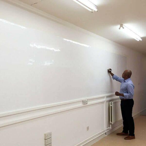 Mies kirjoittaa kiiltävälle valkotaulutapetille