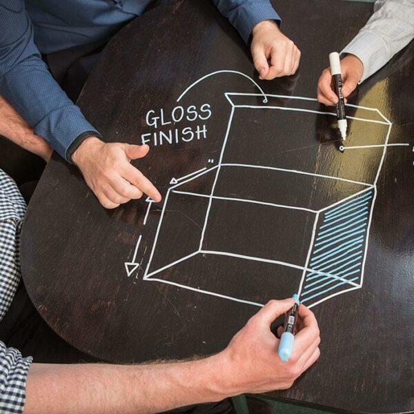 Tussitaulumaalia tuotesuunnittelussa mustalla pöydällä